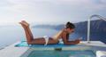 Woman using phone app in bikini on vacation 76223768