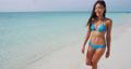 Happy woman walking on beach 76223774