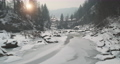 Mountain river in ice, snow at sun pine forest aerial. Winter nature landscape. Bridge with tourists 76227405