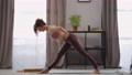 home fitness exercise, woman is training alone in living room, full-length portrait of slender 76229780