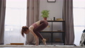 sportswoman is performing asana at home at morning, lifting her body from floor by hands, performing 76229781