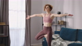 yoga practice of adult woman in living room, sporty lady is doing balance exercise, standing on one 76229782