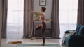 home fitness training of adult woman, lady is performing garudasana at living room of modern 76229789
