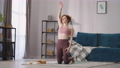 adult housewife is doing physical exercises alone in living room at morning, portrait of slender 76229797
