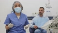 Positive female dentist in face mask standing near medical chair and preparing for treatment 76231974