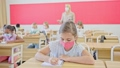 Multiracial group of kids wearing face masks working at class, writing and listening explanations of teacher in classroom 76231981