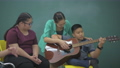 The teacher is treating the minds of disabled children by playing music in the classroom. 76233921