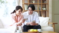 Young couple looking at a smartphone in the living room 76236483