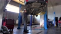man work car suspension repair in car auto service station. FullHD 76240611