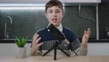 Boy vlogger look at camera and recording podcast video for internet. Kid videoblogger filming new vlog video with professional microphone at home. Young blogger talking on video shooting. 76253595