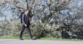 Smiling Businessman Using Smartphone While Walking By Flowering Tree In Park 76262448