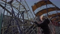 Woman standing in abandoned amusement park, rust-covered roller coaster 76263938