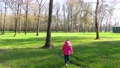 Little Girl Running in a green park towards playground.  76269621
