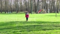Little Girl with a mask dressed in pink running in a green park  76269630