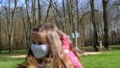 Little girl in a Protection Mask jumping and happy. Then she takes off her mask 76269636