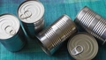 Tin cans with food. Conserved food. Closeup of a group of aluminium cans. 76298677