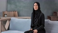 Portrait Muslim woman in traditional black hijab smiling posing on couch. Medium shot on RED camera 76301118