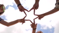 A group of friends make a star shape out of their fingers. 76304303