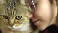 A young woman in glasses presses a cat to her face. British breed cat hugs with a woman. Slow motion 76305532