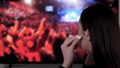 Young woman using wireless earbuds and listening to a concert 76319529