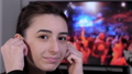 Young woman using wireless earbuds and listening to a concert 76319531