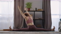 yoga workout of sporty flexible woman at home, lady is doing split and stretching hands, sitting on 76323250