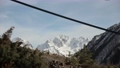 A slackline sling swaying in the wind between trees high in the mountains on a sunny day. Snow-capped mountains in the background. Preparing for walking on the slackline 76330854