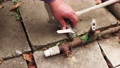 A mans hand unscrews the nut, disconnects the pipe from the tap 76333254