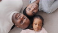 Family portrait african american parents with little daughter girl child lying on floor looking smiling, adult mature dad man afro father pointing up to camera with finger, top view, three generations 76341349