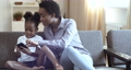 Curly African American mother and little girl sitting at home sofa. Woman showing something to small cute daughter on smartphone screen. Mom with little kid tapping, scrolling playing on mobile phone 76341352