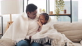 Afro american single mother parent mom woman hugs little black ethnic african girls child daughter sister, family talking secret sitting on couch covered with blanket, baby female kid shows one finger 76341355