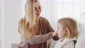 Young caring mother single mom adult woman care for child combing blonde hair of little girl daughter toddler uses comb hairbrush for morning beauty procedures at home preparing kid baby for school 76341357