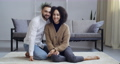 Afro american woman ethnic girl and handsome guy caucasian man sitting on floor in cozy living room near sofa holding mobile phone smart device looking at camera sincerely smiling enjoy time together 76341369