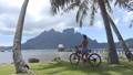 Travel vacation lifestyle. Woman on electric bike aka eBike on travel tourist tour on Bora Bora in French Polynesia, Tahiti. 76346267