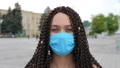 Stylish cute female in protective mask at city street 76353254