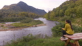 Camping nature woman sitting at picnic table enjoying view of wilderness Quebec 76353488