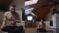 Yoga tutor teacher conducting online courses sitting on mat indoors kitchen background. Confident man teaching practicing healthy meditation exercise wearing headset at home. lockdown healthcare  76354073