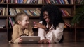 Schoolgirl and babysitter look at tablet display and laugh 76358468