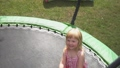 Cheerful girl in a striped dress is jumping and waving hands on the trampoline 76365841