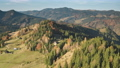 Autumn mountain forest, cottages aerial. Nobody nature landscape at fall colors. Rural grass fields 76365903