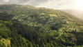 Aerial of mountain town on green grass hill. Nobody nature landscape. Sun shine over spring forest 76365932