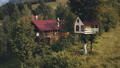 Cottage with treehouse at forest aerial. Wooden tree house on branch. Mountain village at summer day 76365943