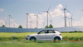 electric car driving through the green countryside 76371531