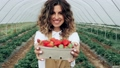Smiling radiant woman showing strawberries in paper box. 76372526