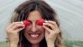 Smiling woman having fun with ripe strawberries. 76372530
