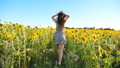 Close up of pretty girl running through field with blooming sunflowers. Young woman in dress having fun jogging through meadow. Scenic summer landscape. Happiness or freedom concept. Back view 76372587