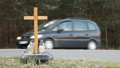 A roadside memorial cross with a candles commemorating the tragic death. 76377519