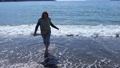 A young white woman walks barefoot along the sea beach in the surf zone in early spring in Fethiye, Turkey. 76382521