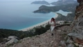 Young white woman with hiking poles and backpack climbs up floor of Lycian Trail over Blue Lagoon in the resort village of Oludeniz, Turkey. 76382524