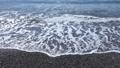 Sea waves run ashore with a pebble beach. 76383015